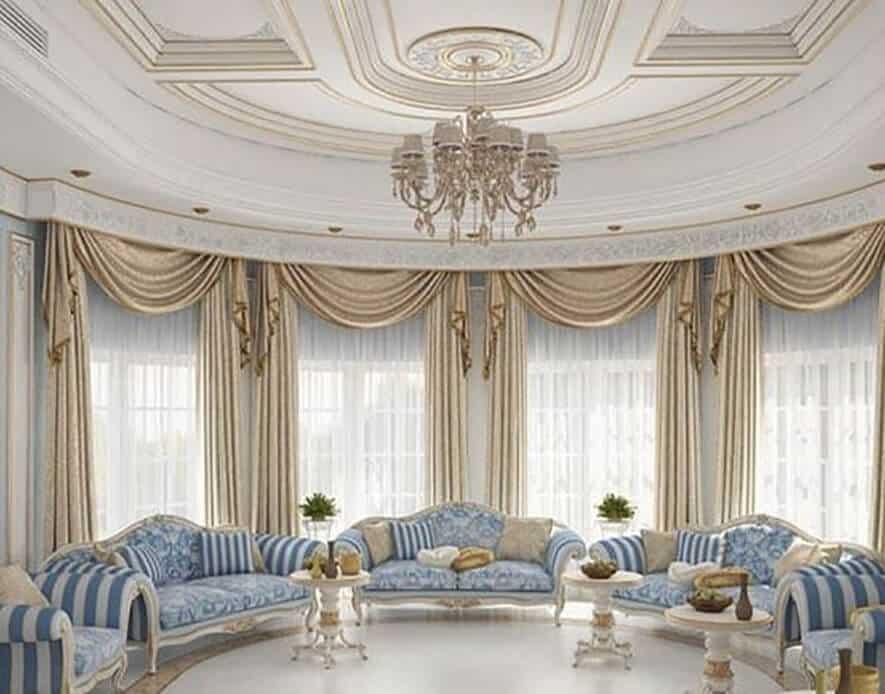 تصاویر نشنان دهنده یک خانه مجلل با مبل های آبی و سفید پرده هوشمند برقی و کف سرامیکی شده با سقفی زیبا و لوستری جذاب است