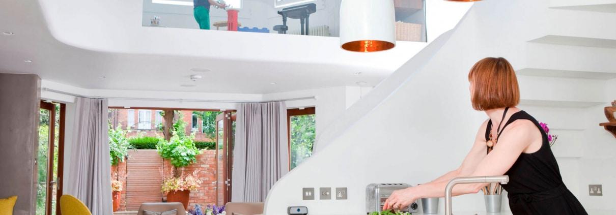 تصویر یک خانم خانه دار که با استفاده از سناریوهای خانه هوشمند در حال گذراندن روزمرگی است.