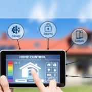 تصویری از تبلت که فردی از راه دور خانه هوشمند خود را کنترل و مدیریت می کند.