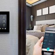 تصویری از اتاق در هتل هوشمند است که بر روی دیوار آن پنل لمسی قرار دارد.