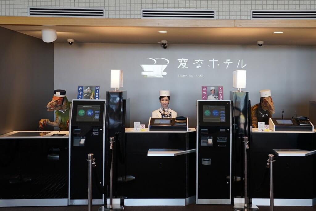 تصویری از هتل هوشمند هن نا در ژاپن است که در آن ربات ها در پشت میز قرار دارند.