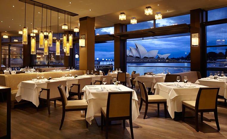 تصویری از رستوران در هتل است که در آن از میز و صندلی های زیبایی با فاصله مناسبی از هم قرار دارند.