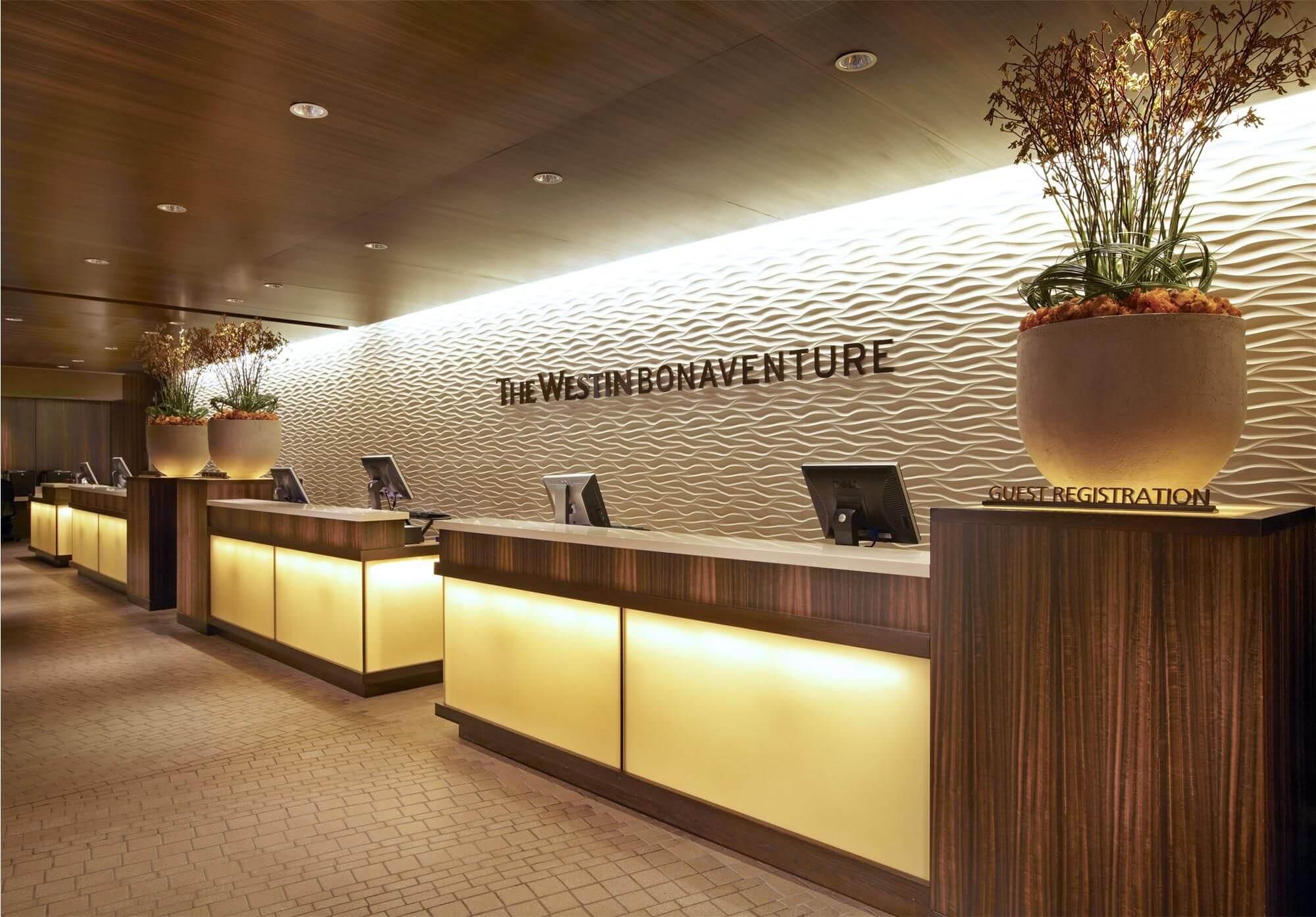 تصویری از پذیرش هتل را نشان می دهد که در آن تعدادی میز، صندلی و سیستم قرار دارد.