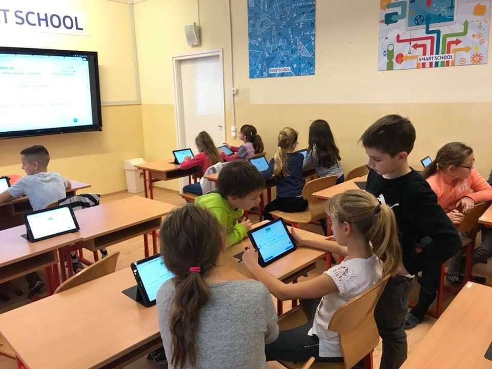 تصویری از کلاس یک مدرسه هوشمند که دانش آموزان در آن مشغول آموزش هستند.
