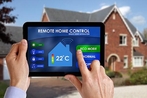 تصویر دست یک مرد می باشد که با هوشمند سازی ساختمان خود و به وسیله یک تبلت، سیستم سرمایشی و گرمایشی دمای محیط خانه خود را تنظیم می کند.