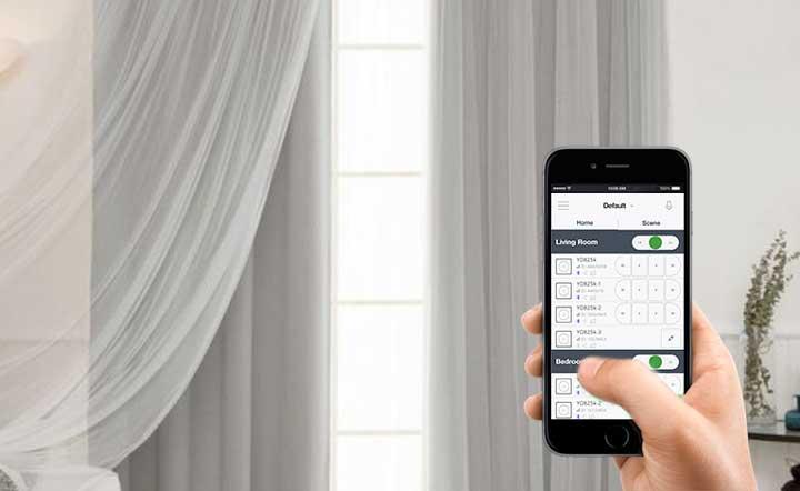یک شخص باموبایل خود از طریق اپلیکیشن در حال کنترل پرده های سفید رنگ است و با این وسیله به هوشمند سازی ساختمان خود پرداخته است