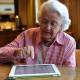 تصویری از یک زن سالمند در حال کار با تبلت جهت مدیریت خانه هوشمند برای سالمندان