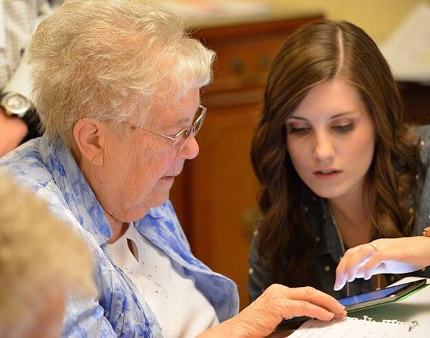 یک دختر در حال آموزش کار با خانه هوشمند ویژه سالمندان به مادر سالخورده خود است
