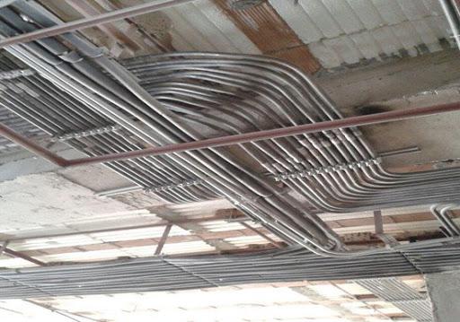 تصویر لوله های برق در سقف کاذب یک ساختمان را نشان می دهد.