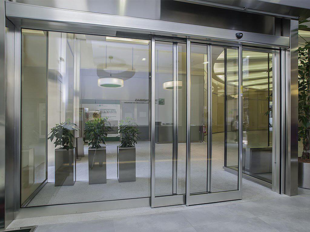 تصویر درب اتوماتیک هوشمند کشویی که شیشه ای است و به عنوان درب ورودی یک مجتمع است.