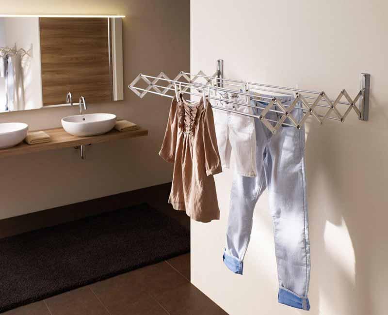 شکل یک لباس آویز دیواری آکاردئونی تاشو از جنس استیل است که سه لباس از آن آویز شده است.