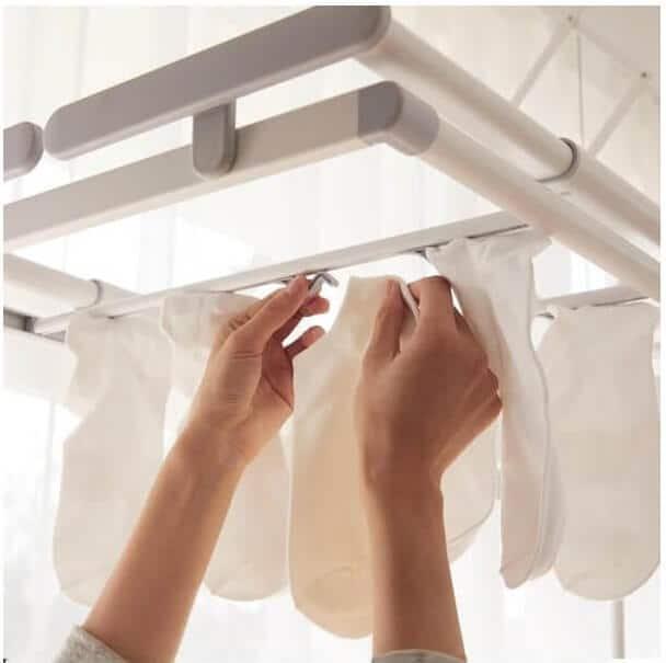 تصویر دستان یک خانم که لباس ها را جهن خشک کردن روی لباس آویز سقفی آویزان می کند.