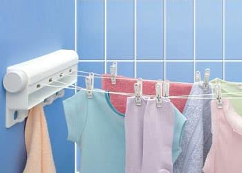 تصویر رخت آویز دیواری پلاستیکی به رنگ سفید است که داری رنگ پس زمینه آبی است و چند لباس روی آن پهن شده است.
