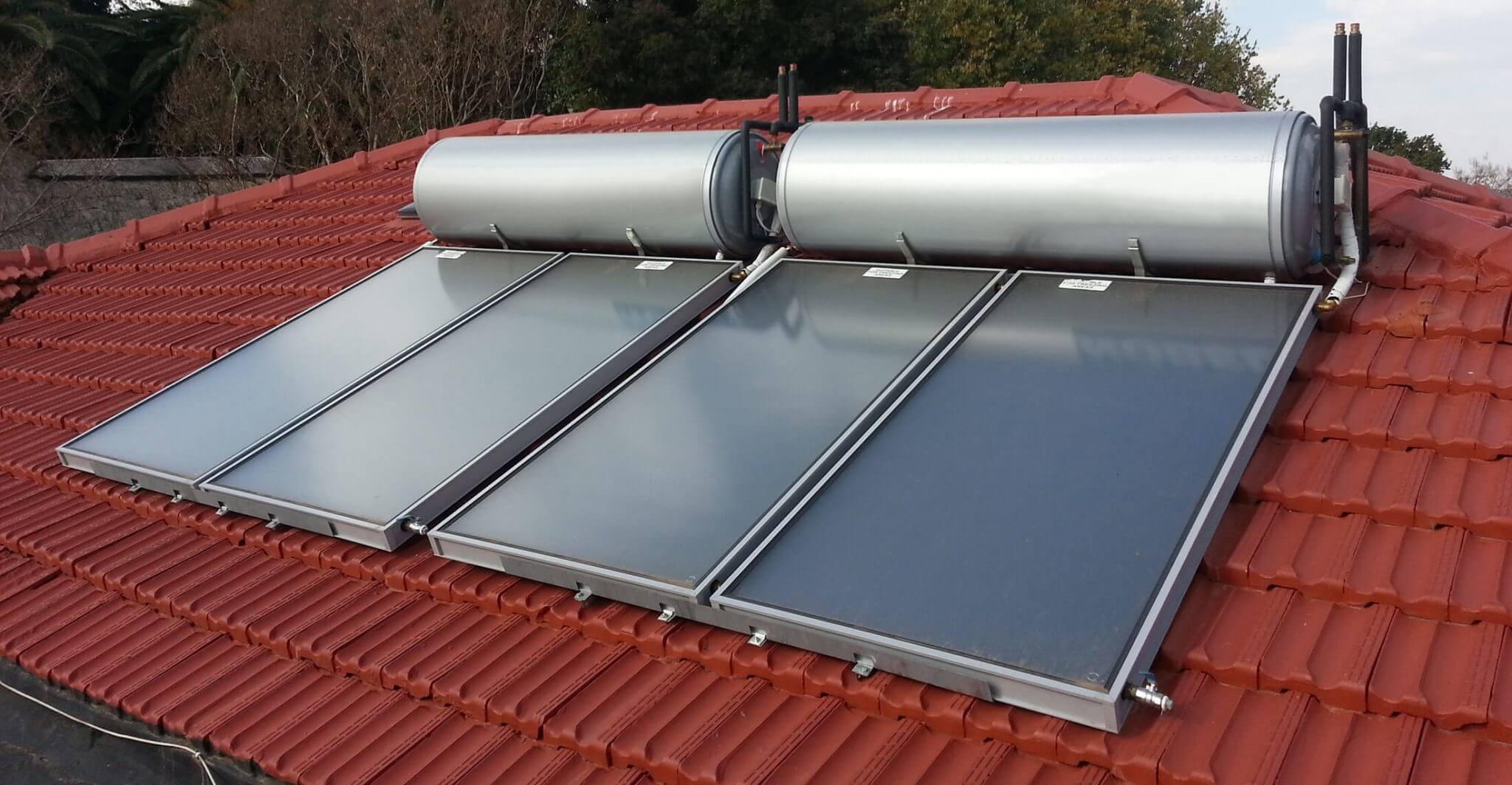 تصویری از آبگرمکن های خورشیدی که به وسیله صفحات تخت کلکتور پوشانده شده است. نمای سقف رنگ قرمز دارد