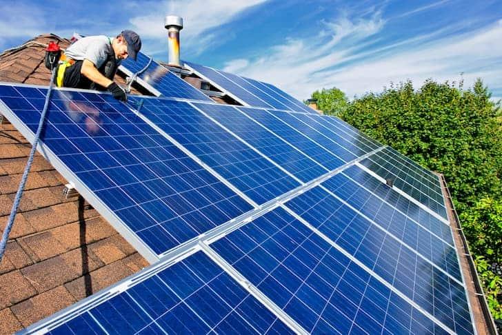 تصویری از یک مرد که پنل های خورشیدی را روی سقف خانه نصب می کند.