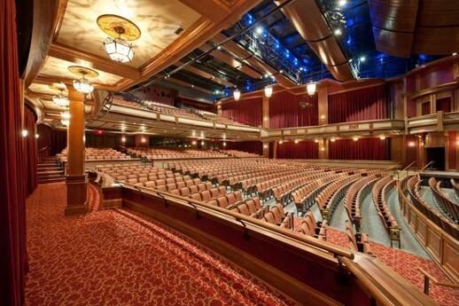 تصویری از سالن آمفی تئاتر با نورپردازی زیبا را نشان می دهد.