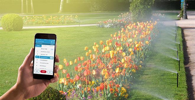 تصویری از سیستم هوشمند آبیاری را نشان می دهد که در حال آبدهی به گل ها در فضای سبز می باشد.