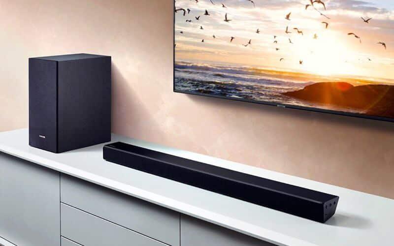 تصویری از یک ساندبار سیاه رنگ که یک سیستم صوتی می باشد و در جلوی تلویزیون قرار دارد را مشاهده می نمایید.