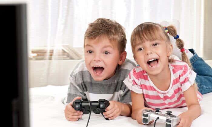 تصویری از یک دختر بچه و پسر بچه می باشد که در دست هر یک از آن ها یک دسته بازی کامپیوتری است.