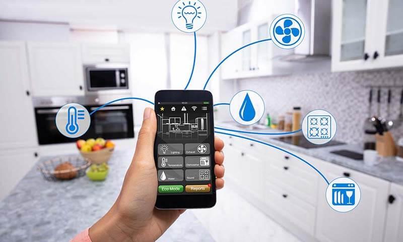تصویری از دست یک خانم که یک تلفن همراه در دست دارد و در آشپزخانه حضور دارد.