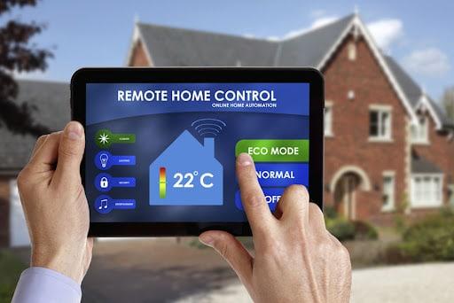 تصویری هوشمند سازی ساختمان های قدیمی است که در آن دستان یک مرد را نمایش می دهد که با تبلت خود مشغول کنترل خانه هوشمند است.